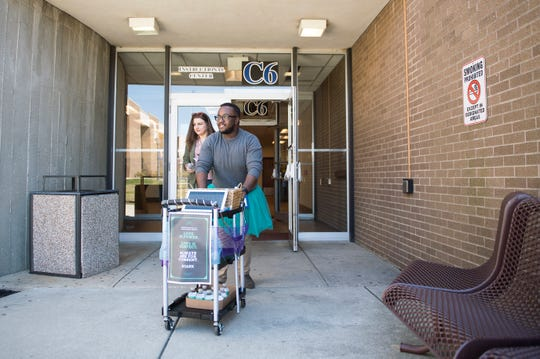 Madison Mulcahy, left, and Michael Beckford II push their 'Consent Cart' at Rowan College at Gloucester County in Sewell, N.J. Monday, April 1, 2019.