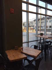 Axe & Arrow's tasting room looks out onto downtown Glassboro and redevelopment of the Rowan Boulevard area. The brewery's tables and bar are made from reclaimed wood.