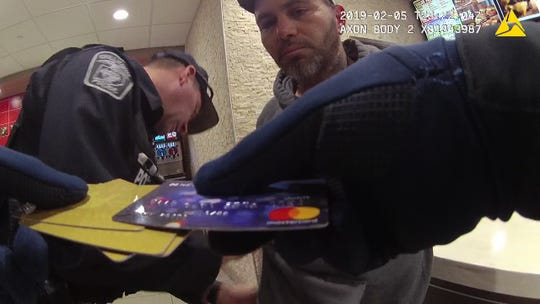 A still frame from a Chillicothe police body camera video shows James A. Rinehart Jr. watching as an officer looks at a Netspend card belonging to murder victim Leann Potts on Feb. 5, 2019, the day after she and two others were murdered at two Londonderry homes.
