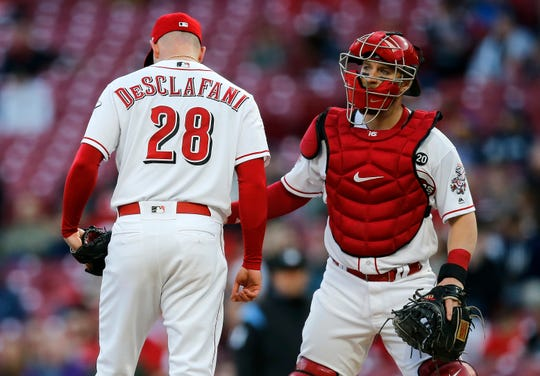 Cincinnati Reds starting pitcher Anthony DeSclafani (28) is visited at the mound by catcher Tucker Barnhart (16) in the third inning of the MLB National League game between the Cincinnati Reds and the Milwaukee Brewers at Great American Ball Park in downtown Cincinnati on Tuesday, April 2, 2019.