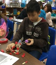 """Jefferson 5th grader Ethan Cha tests his catapult prototype during makerspace activities in early March.  """"Kids are encouraged to think outside the box and use the materials in the room in whatever creative ways they come up with,"""" said art teacher Tracy Ciotti, who designed the activities."""