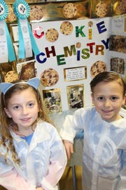 Madison and Jake Greenberg, standing proudly with their Cookie Chemistry project.