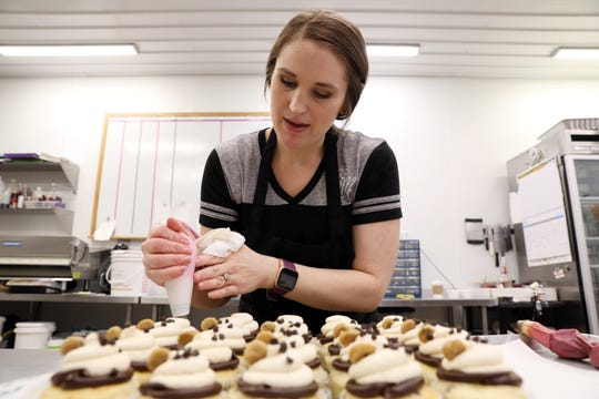 Hannah Marie Miranda, owner of Hannah Marie's Specialty Bakery & Coffee Shop in Coshocton, puts the finishing touches on some cupcakes.