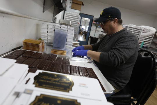 Jeff Rey, 49 of Ann Arbor packages up chocolate cherry bars for the company Midnight Roots made by Choice, a marijuana processing facility in Leoni Township, Michigan on Thursday, March 28, 2019.