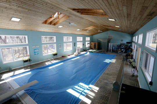 The indoor pool that is part of an adjoining health club at the home in Plymouth Township, Michigan has an automatic pool cover that closes as a safety feature for kids.