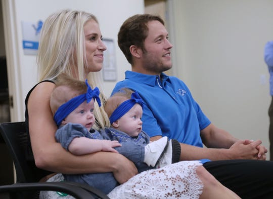 Lions quarterback Matthew Stafford and his wife, Kelly B. Stafford, listen with their twins, Sawyer and Chandler Stafford, during a press conference.