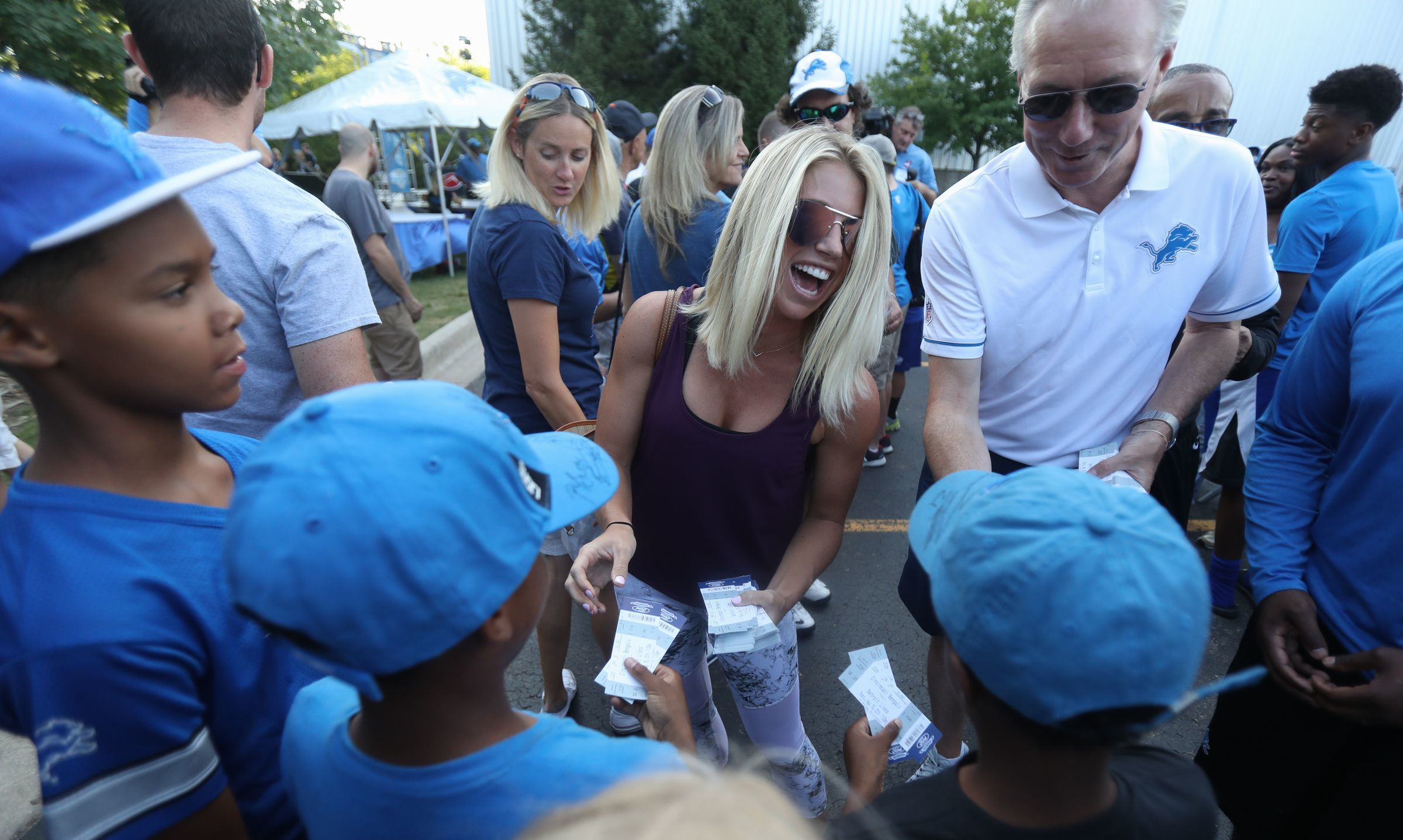 Kelly Stafford, wife of Lions quarterback Matthew Stafford, and Lions president Rod Wood hand out tickets to a preseason game in Allen Park.