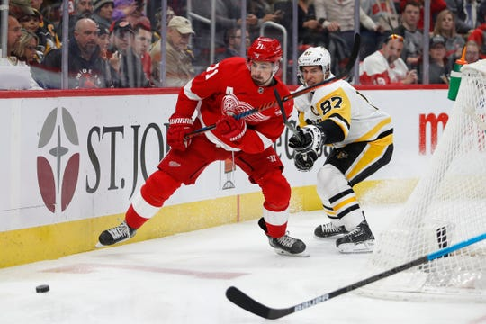 Detroit Red Wings center Dylan Larkin (71) fights for the puck against Pittsburgh Penguins center Sidney Crosby (87) during the second period at Little Caesars Arena, on April 2, 2019, in Detroit.