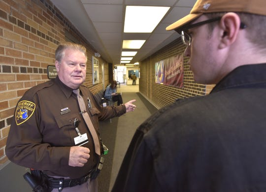 Oakland County Sheriff's Deputy Steve Weitz, left, asks every person entering the Southfield health center, including, Alex Duncan, of South Lyon, if they or their family have been exposed to measles. If the answer is yes, he hands them a mask   and has a nurse would interview them before escorting them for treatment.