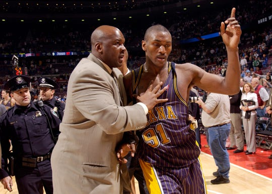 Ron Artest is lead off the court by Chuck Person, Pacers special consultant after a brawl near the end of the game between the Pacers and the Pistons at The Palace of Auburn Hills on Nov. 19, 2004.