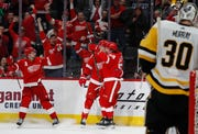 Detroit Red Wings center Dylan Larkin, left, and left wing Tyler Bertuzzi (59) celebrate with right wing Anthony Mantha (39) after his goal on Pittsburgh Penguins goaltender Matt Murray (30) during the third period.