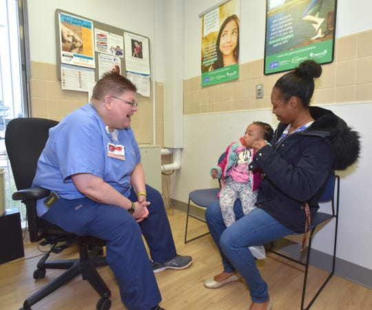 RN Jayne DeBoer-Rowse, left, talks with one-year-old Royalty Jackson and her mother, Diamond Wilford, both of Oak Park, before the toddler gets a series of vaccinations, including one for 'MMR' (measles, mumps and rubella) at the Oakland County Health Division South Oakland Health Center in Southfield.