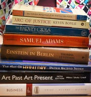 Some of the books purchased by instructor Dawn Raymond from Bookstock.  Student Alex Danish, 18 works with instructor Dawn Raymond of Brightmont Academy, using materials she has purchased from Bookstock in Livonia, a resource for teachers for used books and materials, in Birmingham, Michigan on March 21, 2019.
