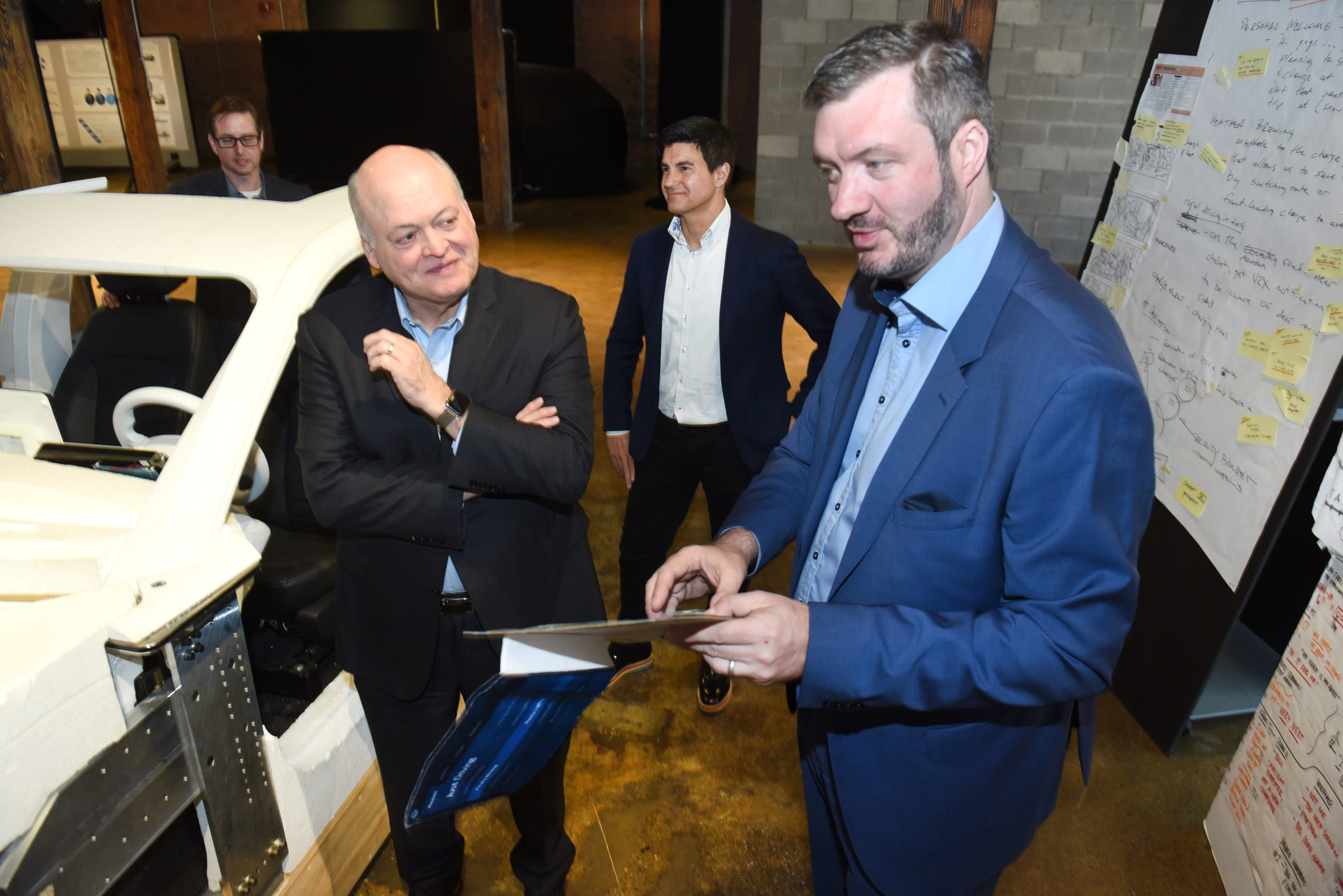 Ford CEO Jim Hackett listens to Darren Palmer, right, Ford's electric vehicle global product development director, talk about the design of Ford's first-ever fully battery-electric SUV,  at Ford's The Factory in Corktown. The  vehicle will go on sale in 2020.