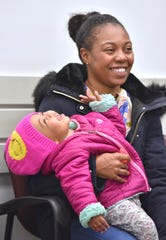 One-year-old Royalty Jackson shares a laugh with her mother, Diamond Wilford, both of Oak Park, as they wait in the medical waiting room before the toddler gets vaccinations, including the 'MMR' (measles, mumps and rubella) vaccine at the Oakland County Health Division South Oakland Health Center in Southfield.
