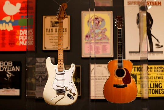 """Guitars used by Jimi Hendrix, left, and Eric Clapton are displayed with concert posters at the exhibit """"Play It Loud: Instruments of Rock & Roll."""""""