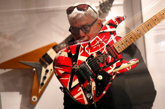 A man inspects a guitar made and played by Eddie Van Halen.