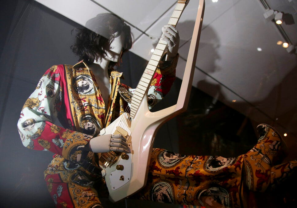 """An outfit and guitar used by Prince is displayed at the exhibit """"Play It Loud: Instruments of Rock & Roll."""""""