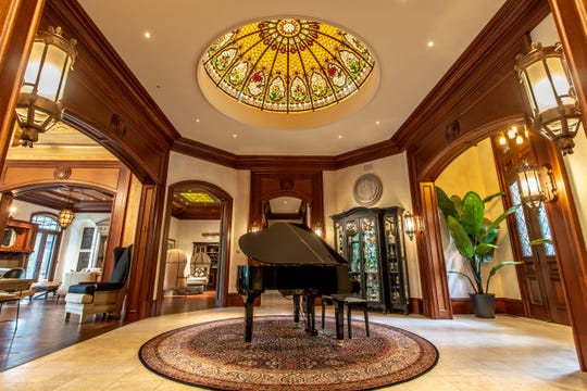 The entryway of this MI Dream Home features a grand piano and stained glass dome in the ceiling.