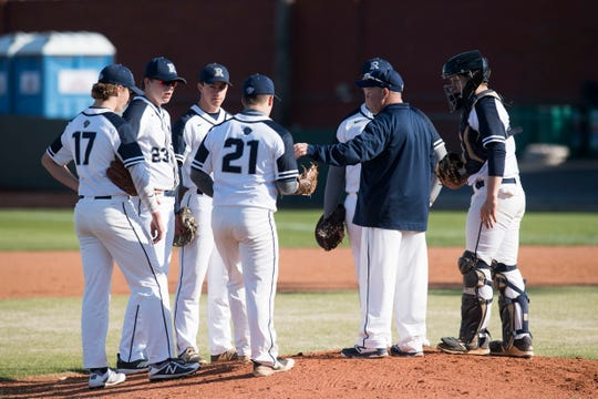 The Reitz Panthers meet at the mounds as pitchers are exchanged during Reitz Panthers vs Memorial Tigers game at Bosse Field in Evansville, Ind., Tuesday, April 2, 2019.