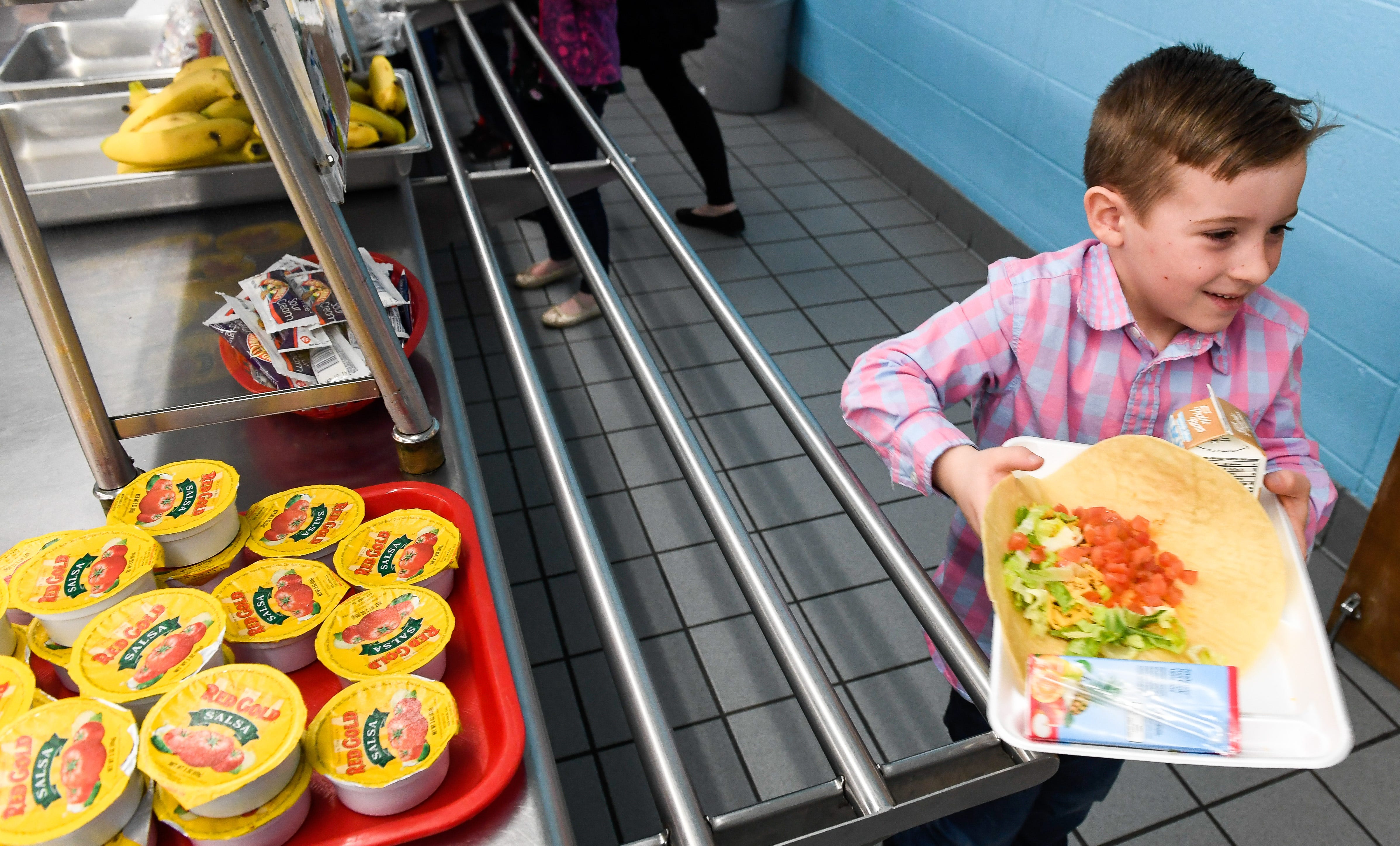 Rider Workins, five years-old, heads toward his table with a freshly made taco at Henderson's East Heights Elementary School Tuesday, March 26, 2019.