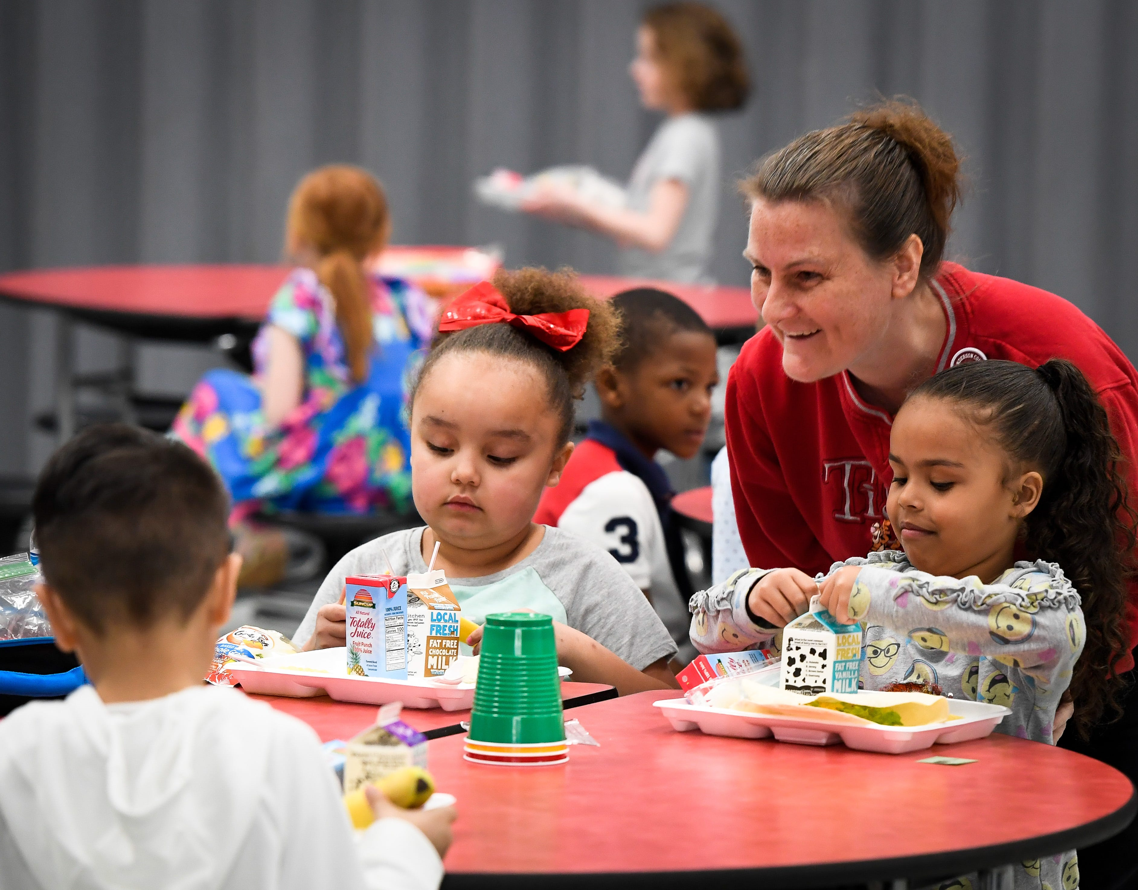 Jennifer Murphy checks in with a table of dinners as she helps monitor the lunchroom at Henderson's East Heights Elementary School Tuesday, March 26, 2019.