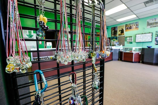 A variety of glass pendants and keychains hang on display at Goblinz Glass in Fond du Lac, Wisconsin.