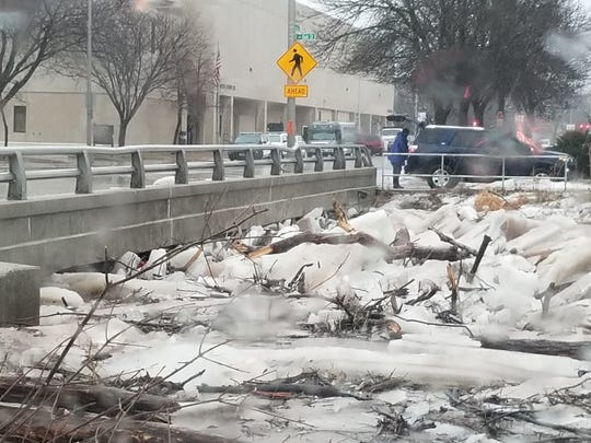 Chunks of ice and debris slam against the Western Street Bridge on March 14, causing the Fond du Lac River to flood streets in the city.