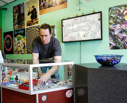 Josh Andrews, of North Fond du Lac ,adjusts a display in his store Wednesday, April 3, 2019 at Goblinz Glass in Fond du Lac. Andrews makes all the glass pieces for sale in his store at his North Fond du Lac studio.
