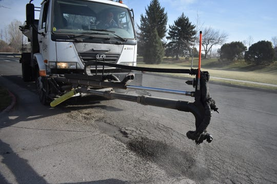 A Fort Collins Streets Department vehicle patches a pothole at Rolland Moore Park on Wednesday.