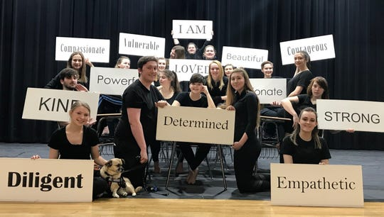 The cast of this year's LEAP: The Human Kindness Project with signs expressing some of the ideas in their production about working toward inclusion to combat loneliness.