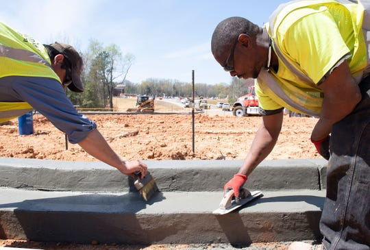 Jesus Sanchez (left) and Ray Jackson Jr., with Capitol Construction, work on a new traffic circle while members of Greenville's City Council tour construction of the bypass being built between Verdae Boulevard. and Woodruff Industrial Lane Wednesday, April 3, 2019.