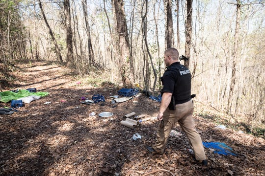 Greenville police officer Ben Sanders of the Community Response Team checks a location of a known homeless camp during his shift Apr. 3, 2019.