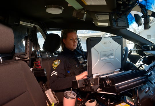 Officer Taylor Hronek works in her car after responding to an alarm call near downtown Great Falls on Tuesday.