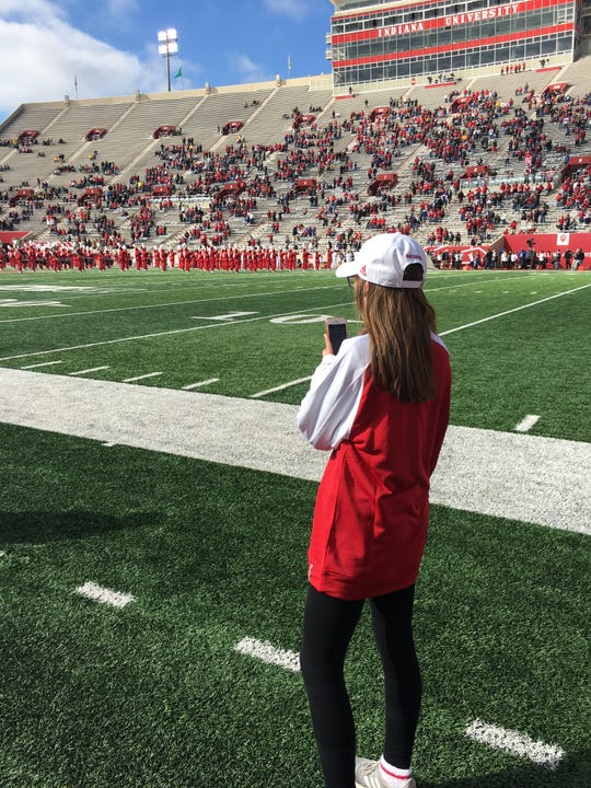 Rachel Gillam works on her Instagram Story during an IU football game.
