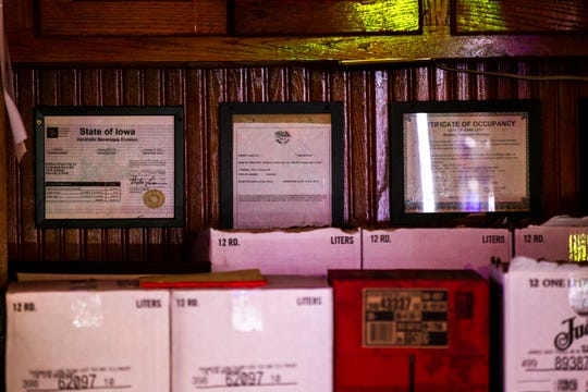 Framed permits from the state and city hang on a wall behind the bar during 'mug club' night on Thursday, Oct. 18, 2018, at Brothers Bar in Iowa City.