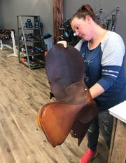 Jessica Stafford of Hazlehurst, owner of Tack of the Town in Ridgeland, checks a saddle that is on consignment at the store.