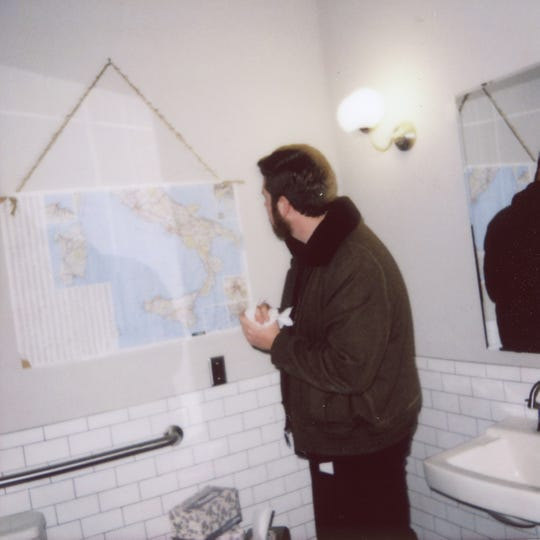 News Sentinel reporter Ryan Wilusz examines a map of Italy in the bathroom of Emilia.