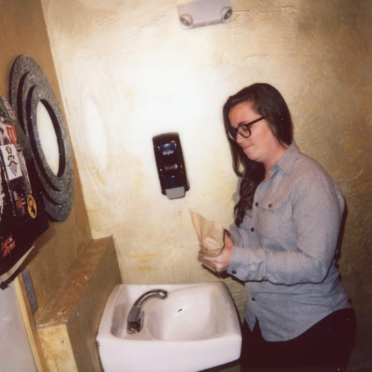 News Sentinel digital producer Kelli Krebs wipes her hands with paper towels in the first floor bathroom of Scruffy City Hall.