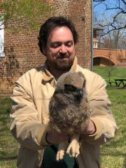 Dr. Mike Bodary poses with the owl he placed back in the tree.
