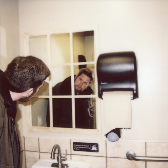 News Sentinel reporter Ryan Wilusz has a difficult time finding a clear view of himself in the mirror in the bathroom of Myrtle's Chicken.