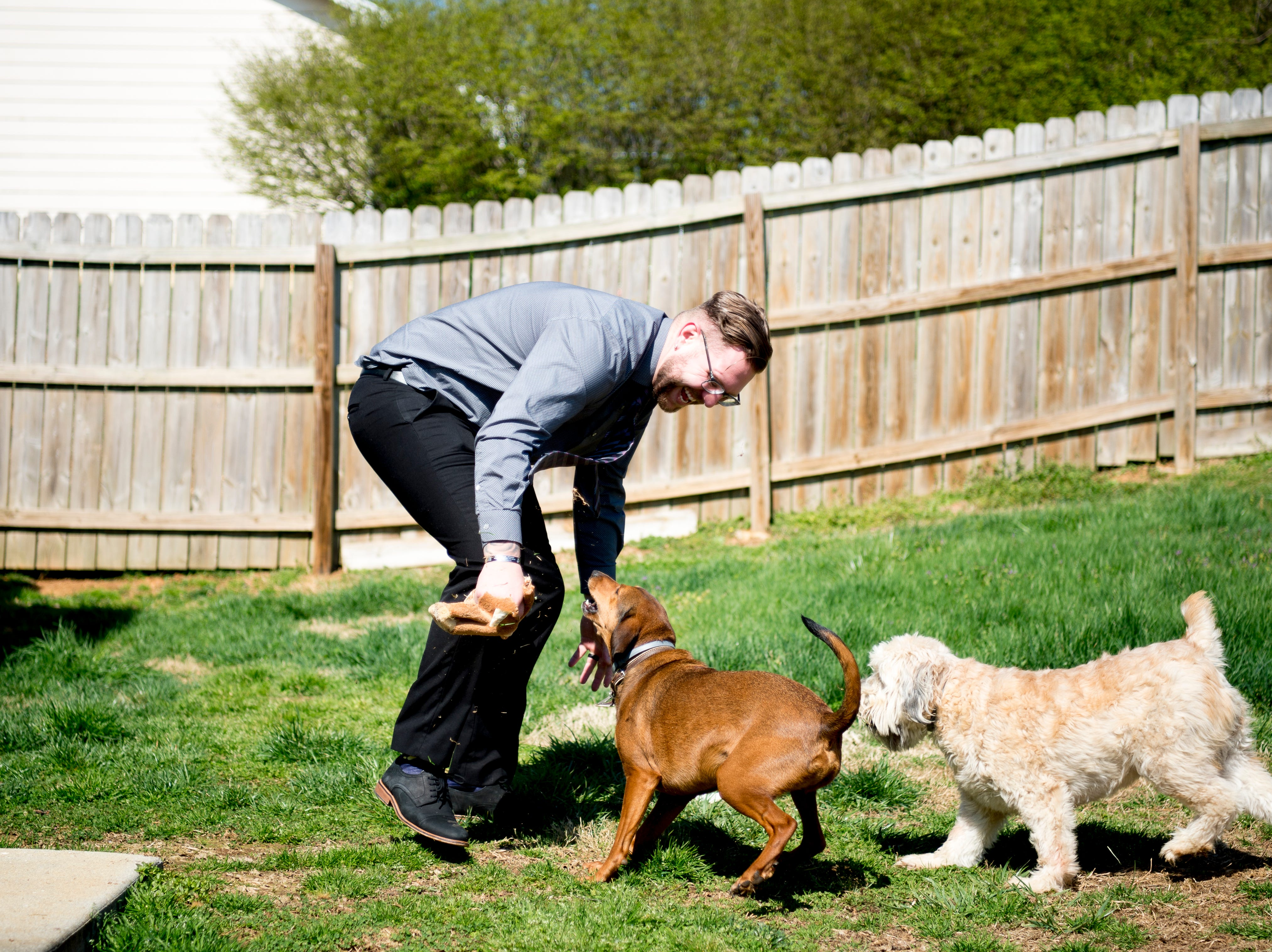 Austin Miller plays with their dogs Nessie, a wheaten terrier, and Dobby, a mountain cur, in the backyard of their home off McKamey Road west of Knoxville, Tennessee on Wednesday, April 3, 2019. After months of house searching, the couple decided to move into their current home last December after making some small compromises like being further away from downtown.