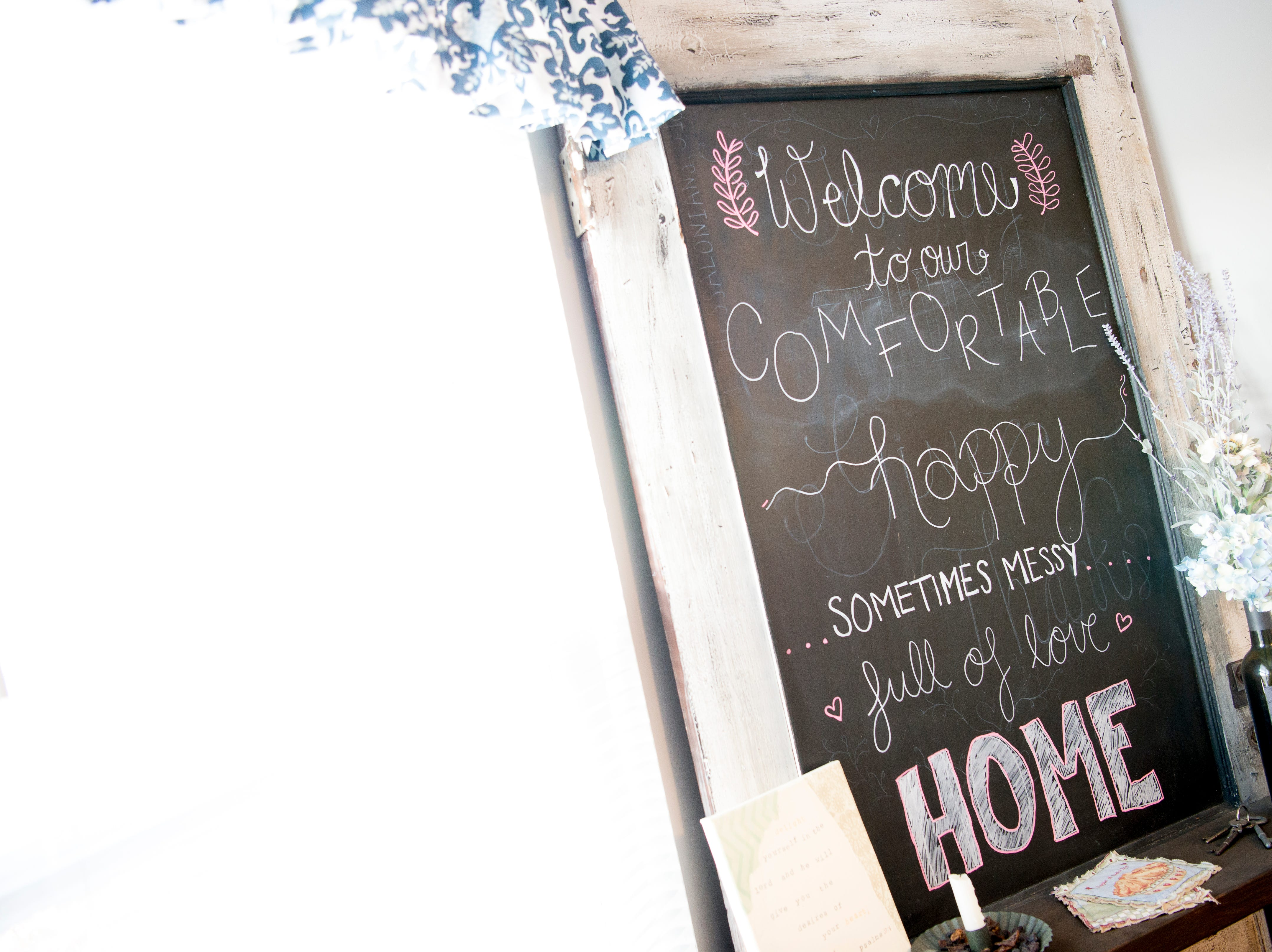 """A sign reading 'Welcome to our comfortable happy sometimes messy full of love home,"""" in the living room of Miller and Gurney's home off McKamey Road west of Knoxville, Tennessee on Wednesday, April 3, 2019. After months of house searching, the couple decided to move into their current home last December after making some small compromises like being further away from downtown."""