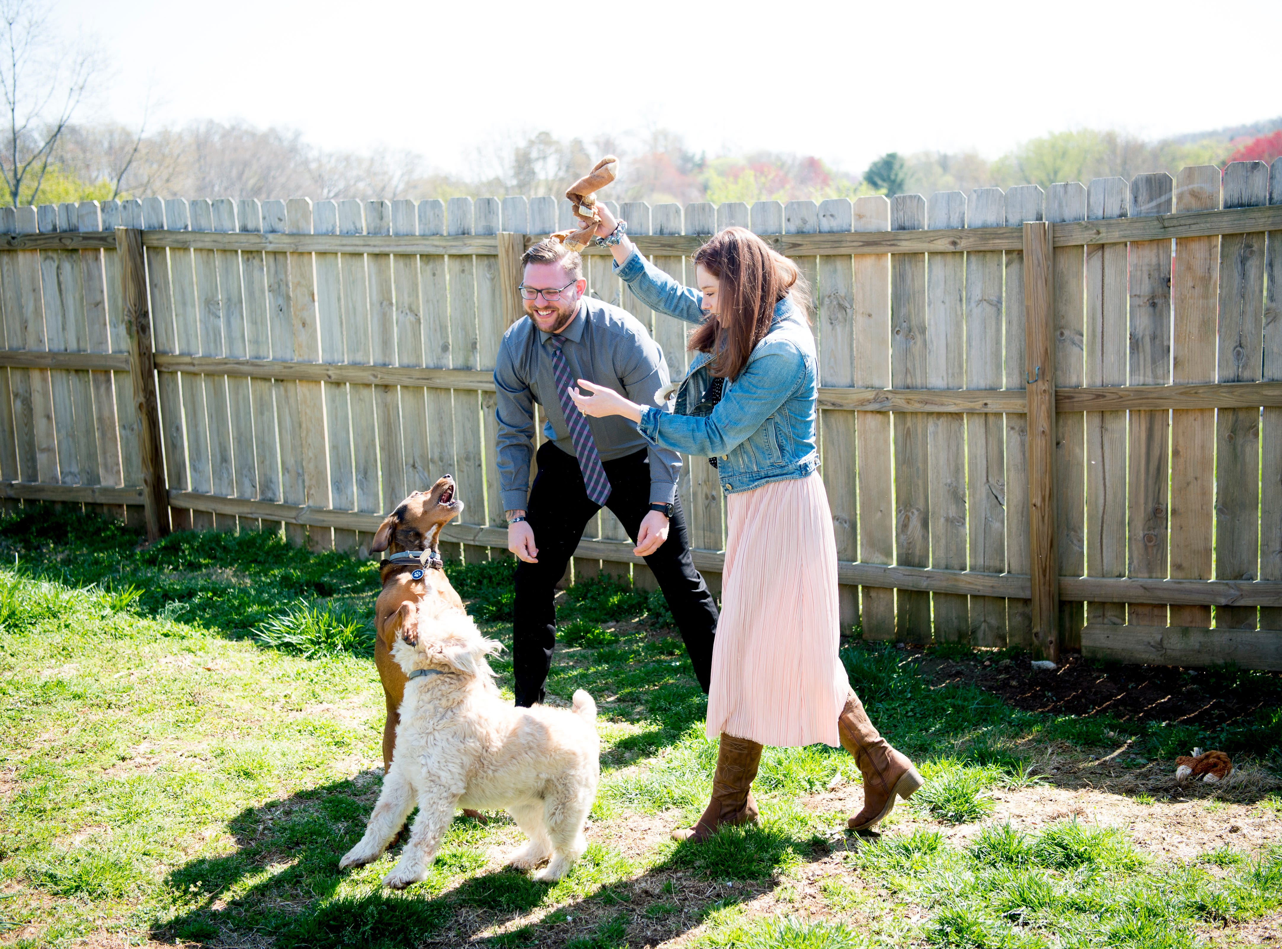 Austin Miller and Trissa Gurney play with their dogs Nessie, a wheaten terrier, and Dobby, a mountain cur, in the backyard of their home off McKamey Road west of Knoxville, Tennessee on Wednesday, April 3, 2019. After months of house searching, the couple decided to move into their current home last December after making some small compromises like being further away from downtown.
