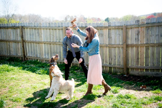 Austin Miller and Trissa Gurney play with their dogs Nessie, a wheaten terrier, and Dobby, a mountain cur, in the backyard of their home. Space for their dogs was a priority when the couple was searching for a house to buy.