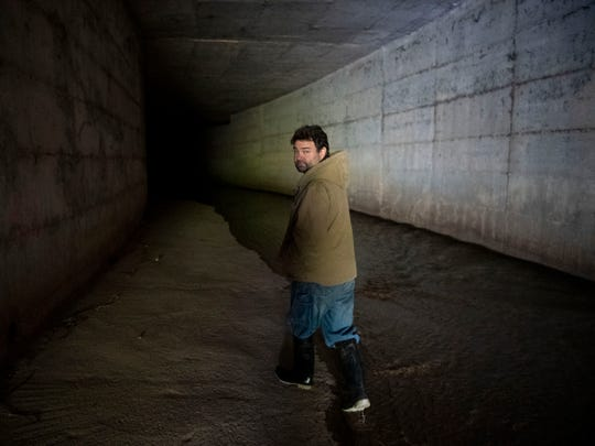 Mark Campen walks into the First Creek tunnel that runs under James White Parkway and Hall of Fame Drive. The tunnel exits near the Downtown dog park.