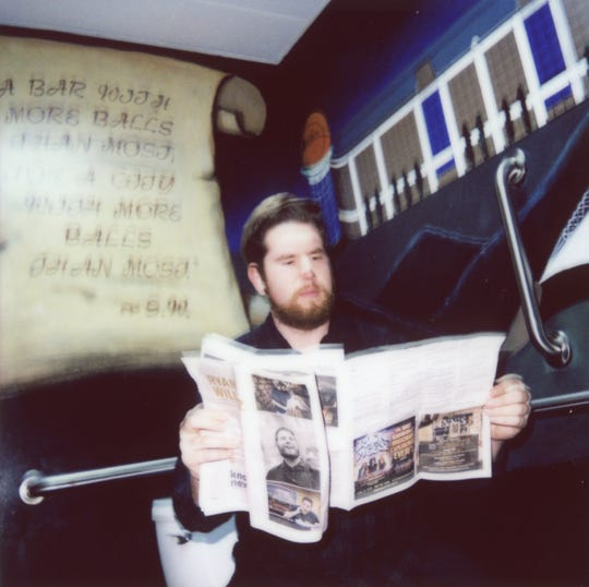 News Sentinel reporter Ryan Wilusz reads a copy of GoKnoxville in the Tommy Trent's men's bathroom.