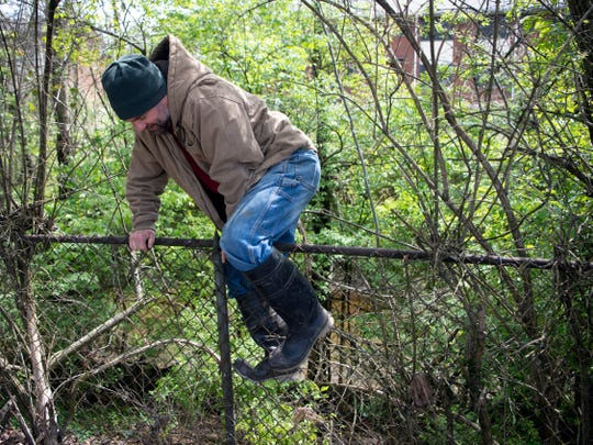 City councilman Mark Campen climbs over a fence to get to First Creek on Tuesday, April 2, 2019 near the Old City.