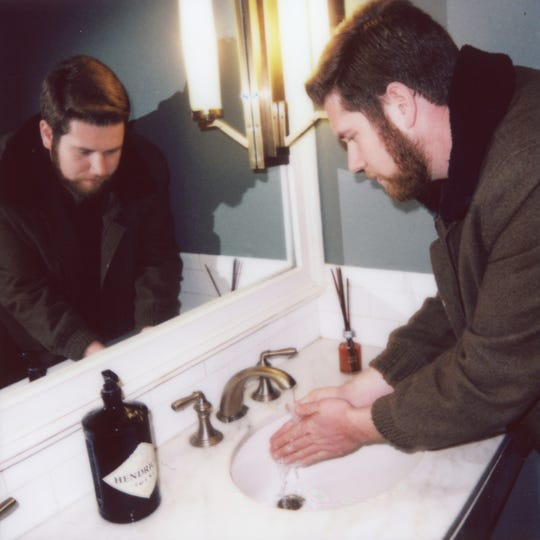 News Sentinel reporter Ryan Wilusz washes his hands with soap from a Hendrick's Gin bottle in the shared bathroom of Oliver Royale, Peter Kern and Tupelo Honey.