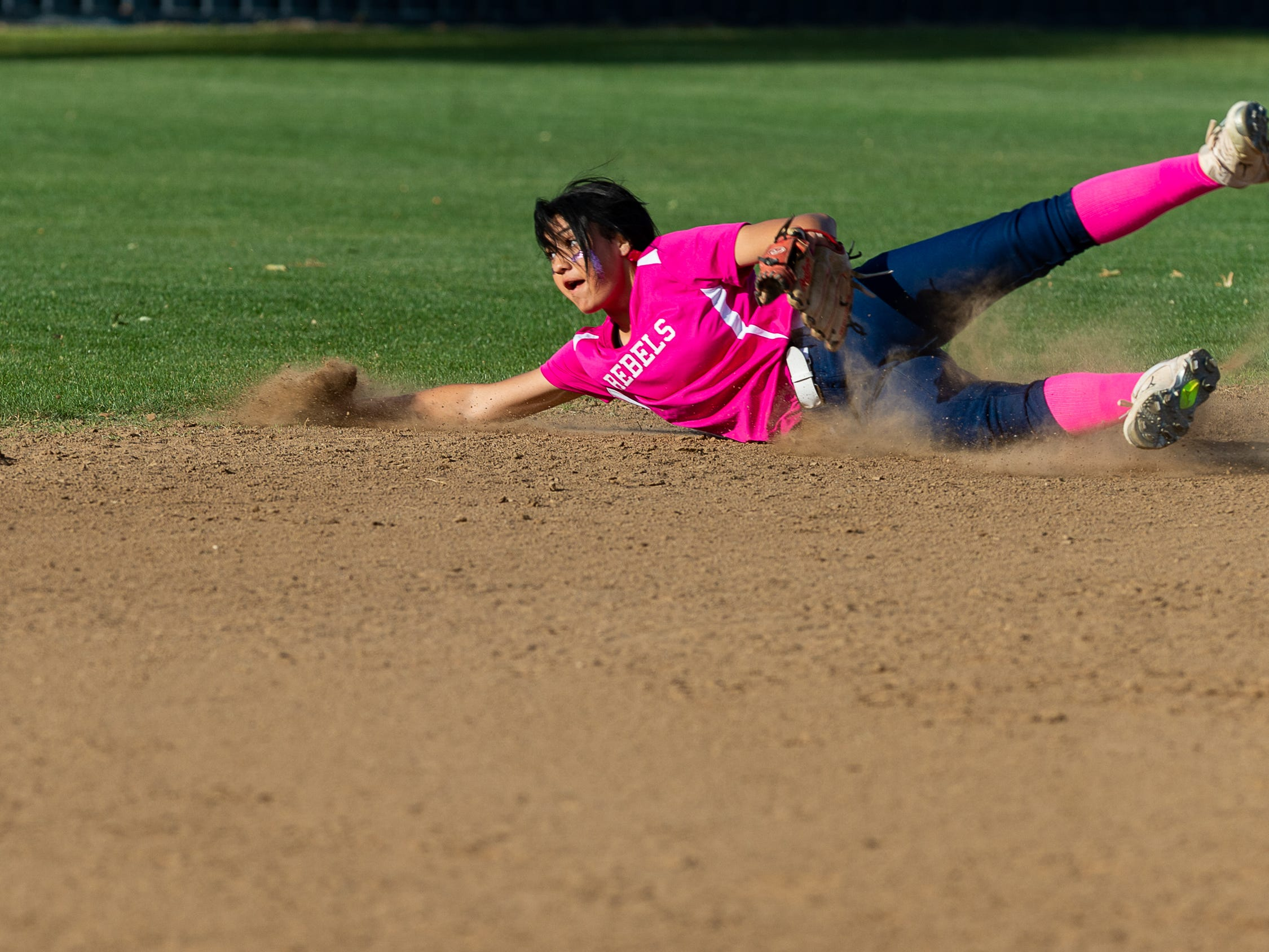 Rebels second baseman Vyctorhea Romero dives for a ball as Teurlings Catholic host St Thomas More Softball. Tuesday, April 2, 2019.